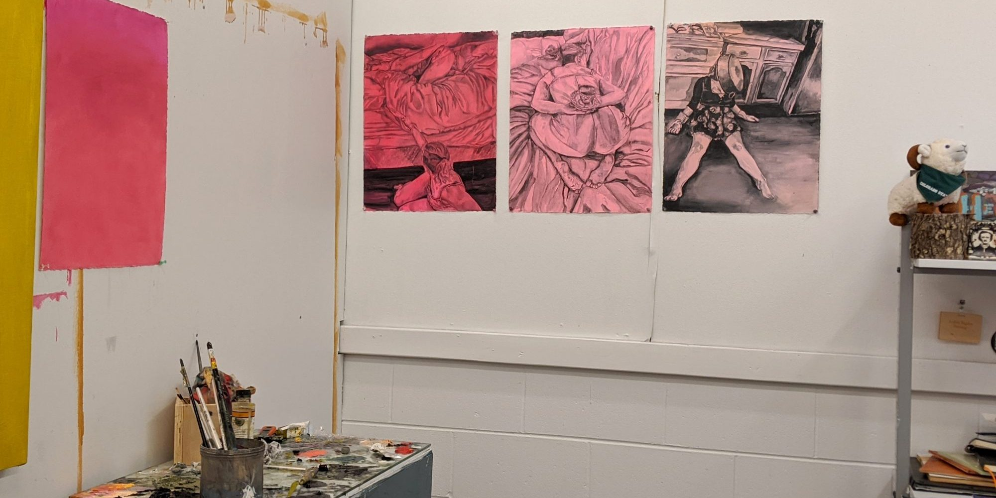 Andrea Bagdon's Painting studio with pink and yellow images on white cinder block walls.