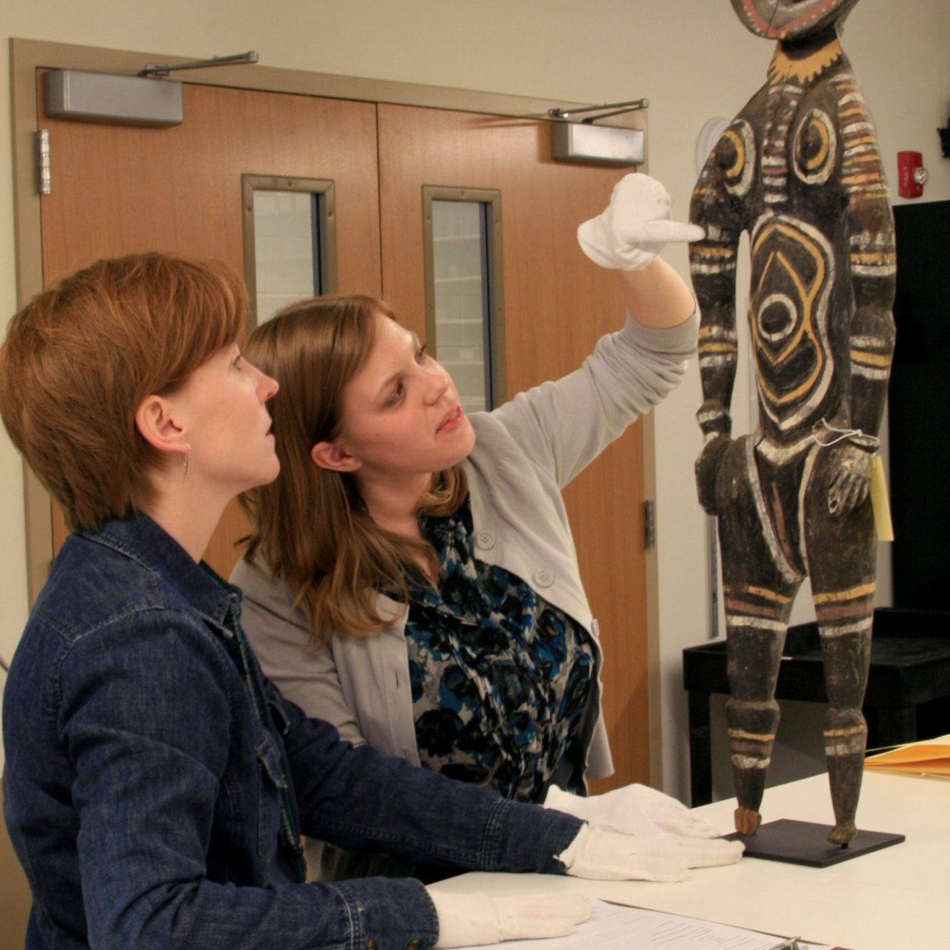 Two students examine an African sculpture