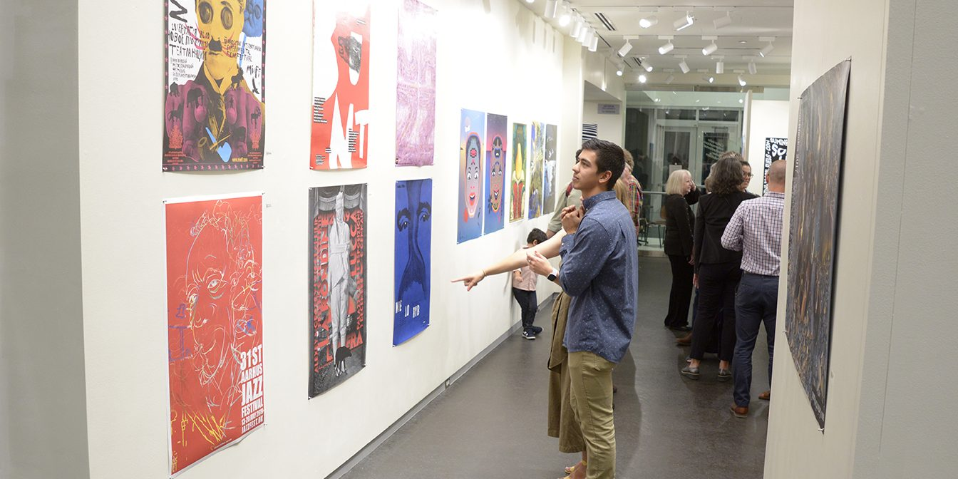 Two attendees look at two rows of posters hung on a wall.