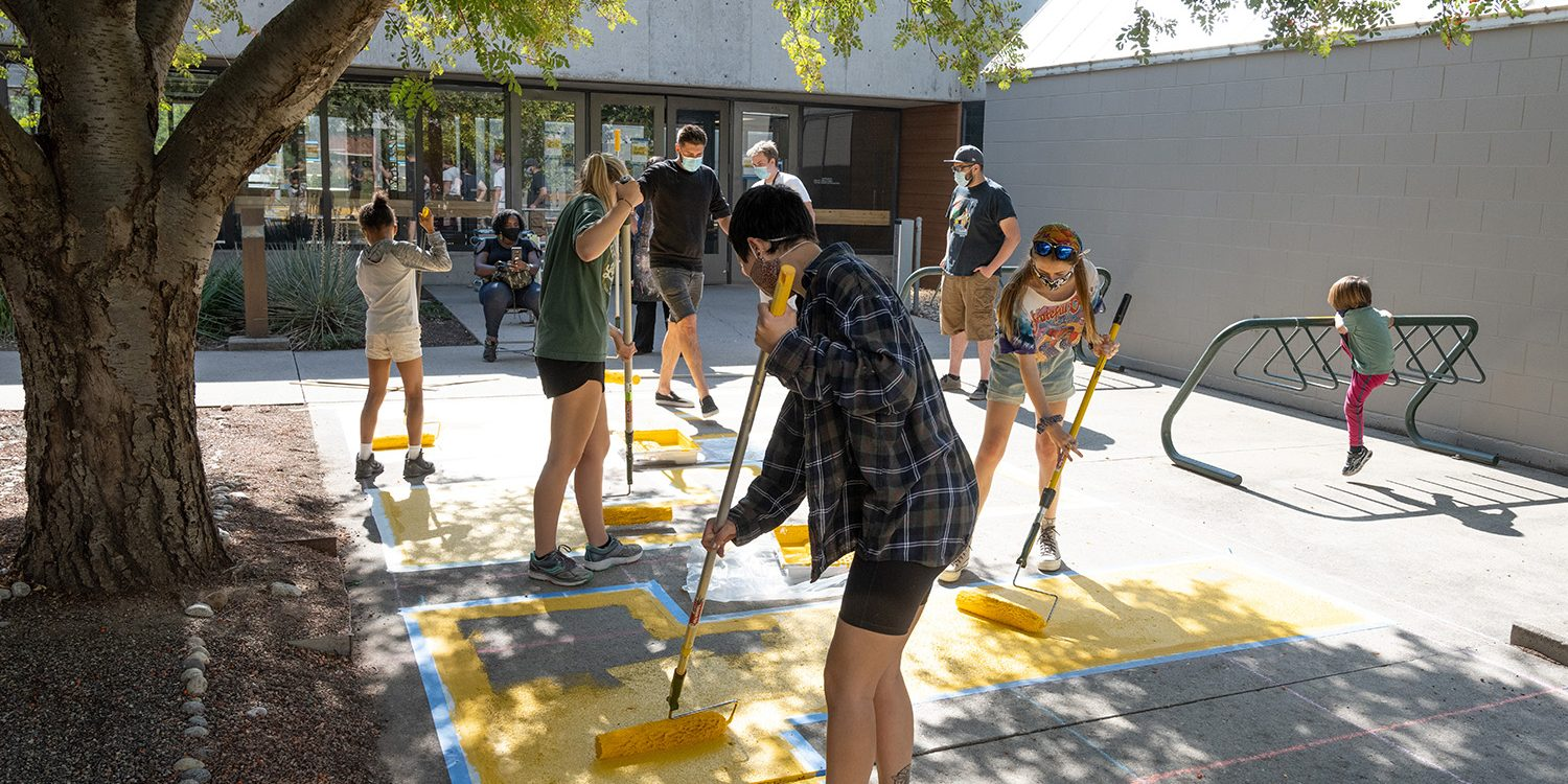 """Faculty and students in a collaborative between Art, Ethnic Studies, and the Black/African American Culture Center, paint """"Black Lives Matter"""" on the sidewalk outside the Art Building, October 10, 2020"""